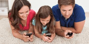 Pappa, mamma och dotter surfar på sina mobiler med familjeabonnemang.