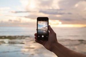 Hand som håller iphone på en strand med frihetskänsla, som ett mobilabonnemang utan bindningstid.