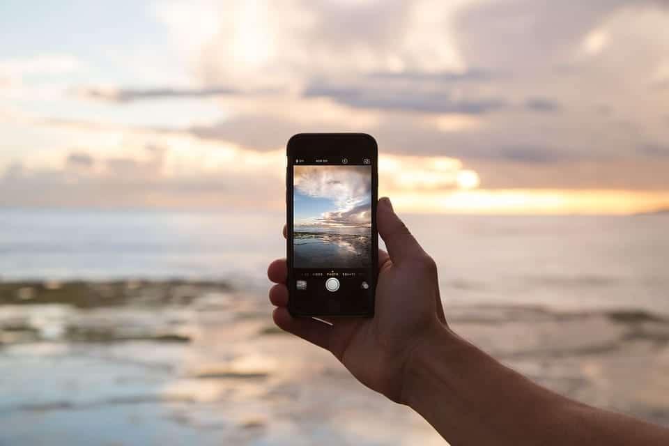 Hand som håller iphone med abonnemang utan bindningstid på en strand