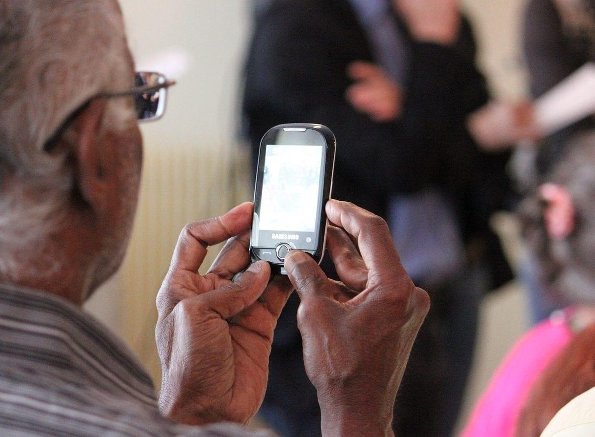 Äldre pensionär med mobilabonnemang i sin Samsung telefon.